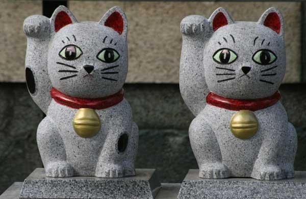 圆型的招财猫绘马 今户神社的绘马与其他神社不同,为圆形,上面还印有两只招财猫,被一圈红绳包围。此外,也有很多人愿望达成后,还可以选择成就绘马,上面印着的是身穿十二单衣的招财猫。  抽签与猫咪护身符 许多女性在参拜神社时都会抽签。今户神社的抽签箱也是猫咪的样子,里面还附送一个巫女造型的招财猫护身符。这里的最吉利的签为大大大吉,抽到这一签的人想必会非常开心。  沿着主殿楼梯走下去,可以看到两只并排摆放的招财猫石像。据说,只要轻轻抚摸两只招财猫,并将照片作为手机待机画面,每天祈祷,愿望就会成真。